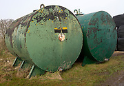 Large green metal water bowsers on chalk farmland, north Wessex Downs AONB, Wiltshire, England, UK