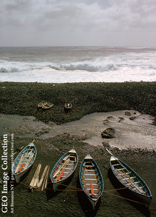 Boats on a rocky beach with pounding surf in the distance.