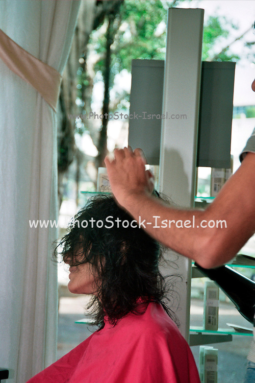 woman having her hair dried and set by male hair dresser