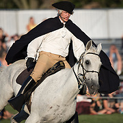 A mounted soldier reenacts Paul Revere's famous ride alerting colonial militia of the coming British forces during the American Revolutionary War. The U.S. Army's Twilight Tattoo is held on Tuesday evenings in the summer at Joint Base Myer-Henderson Hall in Arlington, Virginia. The event features various Army regiments and personnel, with live music, marching bands, and historical reenactments.