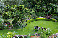 An aerial view of a wooded area, lawn and pond in Derry Watkin's Special Plants Garden in Cold Ashton, Chippenham, Somerset, UK