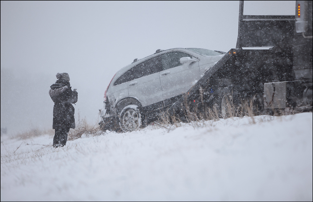 Emotional driver watching her car being lifted onto a flatbed tow truck after sliding into a ditch on Interstate 94.