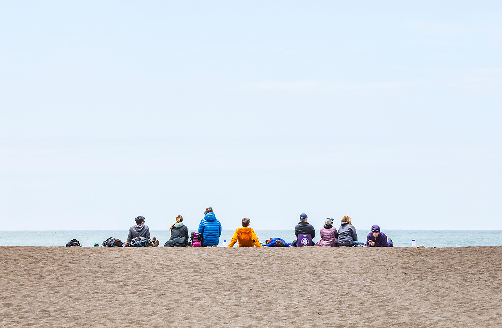 A group of people sitting on Rodeo Beach in the Marin Headlands, Golden Gate National Recreation Area, California, USA.