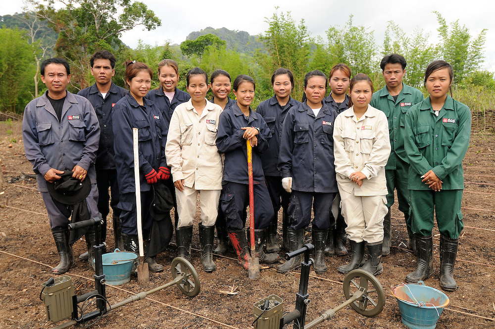 """Members of one of the female demining teams in Khammuan Province, Laos...Laos was part of a """"Secret War"""", waged within its borders primarily by the USA and North Vietnam.  Many left over weapons supplied by China and Russia continue to kill.  However, between 90 and 270 million fist size cluster bombs were dropped on Laos by the USA, with a failure rate up to 30%.  Millions of live cluster bombs still contaminate large areas of Laos causing death and injury.  The US Military dropped approximately 2 million tons of bombs on Laos making it, per capita, the most heavily bombed country in the world. ..The women of Mines Advisory Group (MAG) work everyday under dangerous conditions removing unexploded ordinance (UXO) from fields and villages...***All photographs of MAG's work must include (either on the photo or right next to it) the credit as follows:  Mine clearance by MAG (Reg. charity)***."""