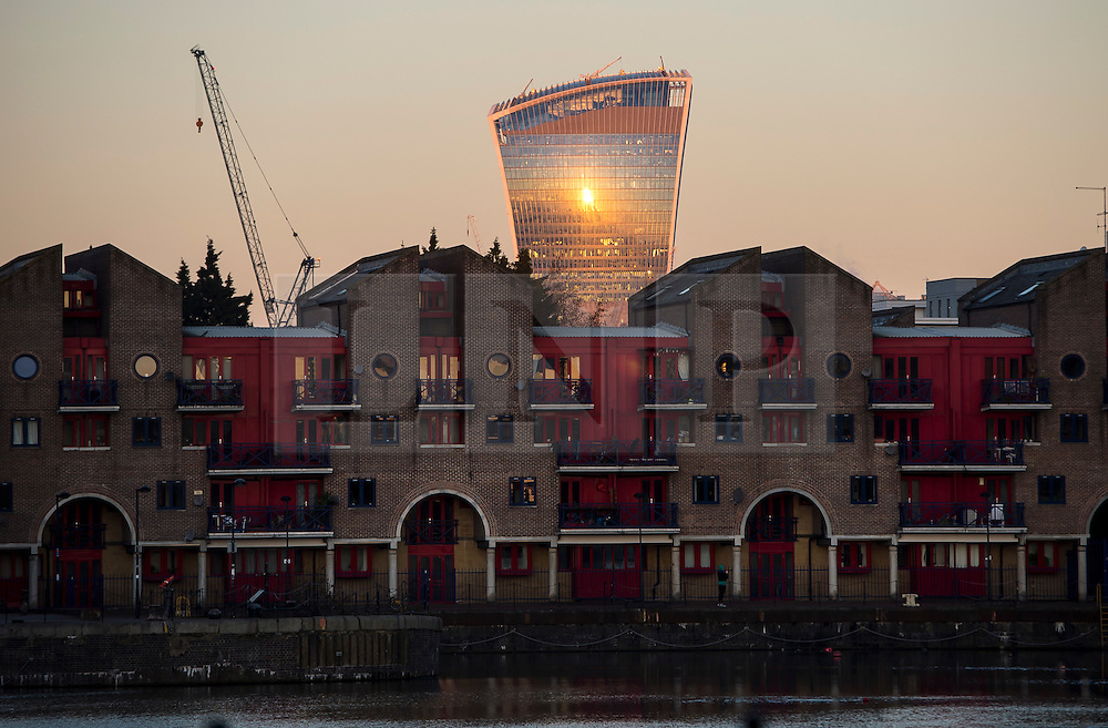"© Licensed to London News Pictures. 07/03/2016. London, UK. The Sun reflected off 20 Fenchurch Street, also known as the ""walkie talkie building' behind residential housing, at sunrise in London on a clear morning on March 07, 2016. Photo credit: Ben Cawthra/LNP"