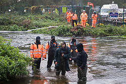 A female anti-HS2 activist stands up after having been pushed by HS2 security guards into the river Colne at Denham Ford during bridge building works for the HS2 high-speed rail link on the first day of the second national coronavirus lockdown on 5 November 2020 in Denham, United Kingdom. Prime Minister Boris Johnson has advised that construction work may continue during the second lockdown but those working on construction projects are required to adhere to Site Operating Procedures including social distancing guidelines to help prevent the spread of COVID-19.
