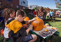 5th grade students Molly Hagan, Ethan Ellingson and Alana Sawyer carve out their pumpkins on Thursday afternoon at Gilford Middle School for the Laconia Pumpkin Festival this weekend.  (Karen Bobotas/for the Laconia Daily Sun)