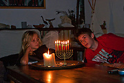 Child lights the candles in a Chanukkah Menorah