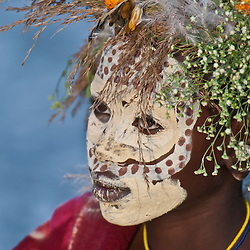 A young girl from the Suri (Surma) tribe with a beautiful tribal headdress and facial art. Omo Valley, Ethiopia