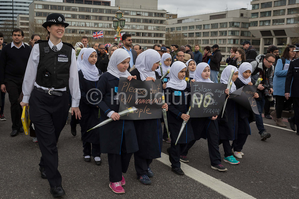 Londoners and police gather on Westminster Bridge, the scene of the Terrorist attack 7 days ago in which 4 people died and others severely injured, on 29th March 2017, London, England. Hundreds crossed the Thames in a silent vigil to commemorate those who died at 2.40pm when Khalid Masood drove into crowds on the bridge before stabbing a police officer at the nearby Palace of Westminster. The crowds fell silent, many bowing their<br /> heads, among them were dozens of young Muslim children and members of the Ahmadiyya community.