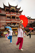 An elderly woman performs the Chinese Fan Dance for exercise in historic Yu Yuan Gardens Shanghai, China