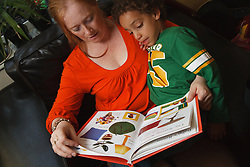 Woman and boy sitting reading a book