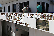 """The facade of the Belize Sugar Cane Farmers Association (BSCFA) office in Corozal displays a plaque that reads: """"Building Inauguration Funded with Fair Trade Funds on February 14th, 2011."""" Belize Sugar Cane Farmers Association (BSCFA), Corozal, Belize. January 21, 2013."""