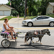 """Lori McDermott of Shawnee led """"Cody,"""" a Class A miniature horse, on a westbound walk in Shawnee on 67th Street near Mullen on Friday afternoon as one of Cody's three weekly walks. Cody, a therapy horse in training who visits nursing homes, gets exercise and desensitized to loud noises during the walks on city streets."""