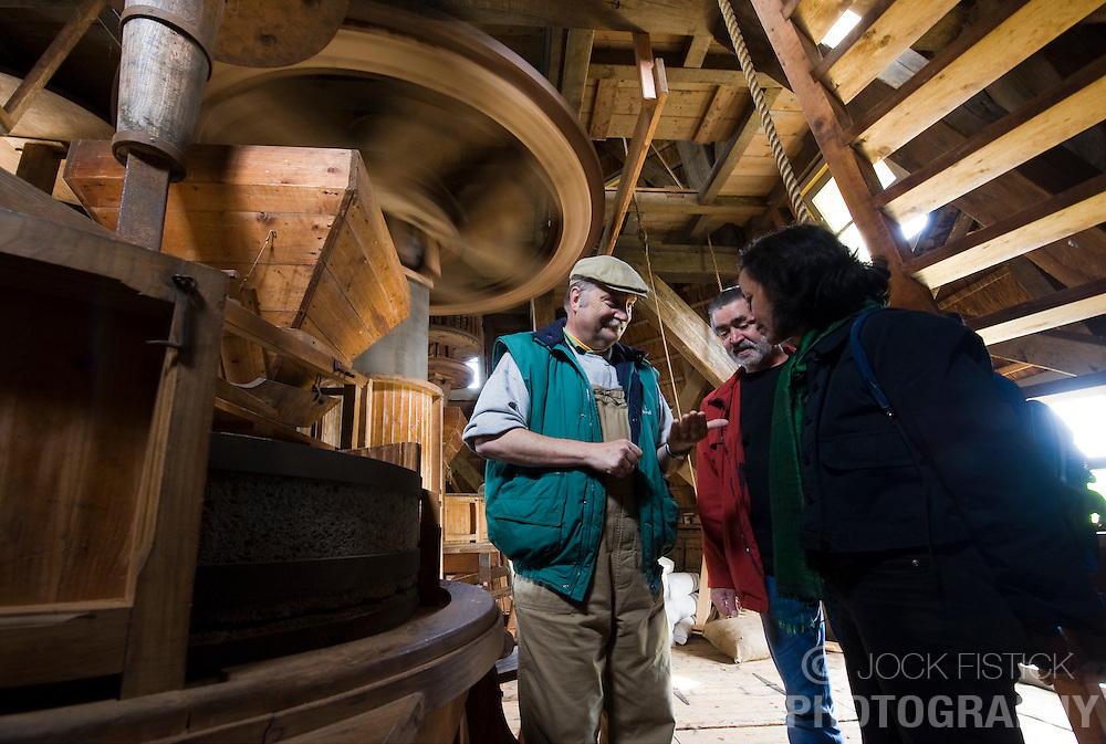 """Nico Kemp, left, a volunteer miller at the De Ster Snuff and Spice mill in Rotterdam, The Netherlands, gives Ebi Jacobi, center, and Frouke Beyen, right, both of Rotterdam, a tour of  the grinding or stage floor, where two small """"Cullen"""" millstones are used for grinding spices. (Photo © Jock Fistick)"""