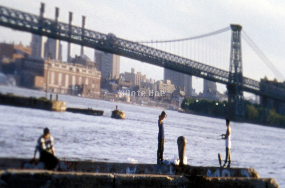 figures overlooking river at the Williamsburg Bridge