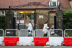 © Licensed to London News Pictures. 29/08/2020. London, UK. Women walk next to the barriers, which are erected for social distancing at the entrance of Chestnuts Primary School in Tottenham, north London, as the school prepares for reopening next week, at the start of the new academic year. The council and the school are putting in place measures for social distancing and safe conditions following the coronavirus pandemic. Photo credit: Dinendra Haria/LNP