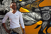 Cuban man posing for portrait against a colourful backdrop. Callejon de Hamel, a street art project in old Havana, which has a Rumba show on a Sunday afternoon, and has strong links to the Santeria religion / cult. The work is made by local Cuban artist Salvador Gonzales Escalona.