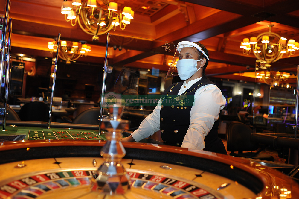 South Africa - Cape Town - 30 June 2020 -  Dealer Manda Kleinhans wearing protective gear. Grand West Casino. Sun International's urban casinos are reopening with restricted tables and slot machine capacities, and with physical shields installed between slot machines and between seats at gaming Tables. Every second slot machine has been disabled to ensure appropriate physical distancing between guests on the casino floor. Safety measures include temperature tests conducted at entrances, while only members of Sun International's loyalty programme - Most Valued Guests (MVGs) - will be allowed access onto the casino floor for the foreseeable future.  They will also be required to complete a medical screening questionnaire in advance of their visit. Casino properties opening today include The Boardwalk in Port Elizabeth, Carnival City in Ekurhuleni, GrandWest in Cape Town, Sibaya in Durban and Time Square in Pretoria. Casinos opening on Wednesday 1 July are Flamingo Casino in Kimberley, Golden Valley Casino in Worcester, Meropa Casino in Polokwane and Windmill Casino in Bloemfontein. Picture: Henk Kruger/African News Agency (ANA)