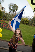 General election 2015. West Kilbride, Scotland. Eve of election calvacade around the town by the SNP (Scottish National Party). Girl with a Saltaire.