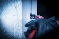 Burglar with crowbar breaking into home