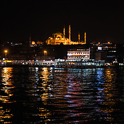 A night view of Suleymaniye Mosque from Galata Bridge. Spanning the Golden Horn and linking Eminonu with Karakoy, the Galata Bridge is a dual-level bridge that handles road, tram, and pedestrian traffic on the top level with restaurants and bars on the level below.