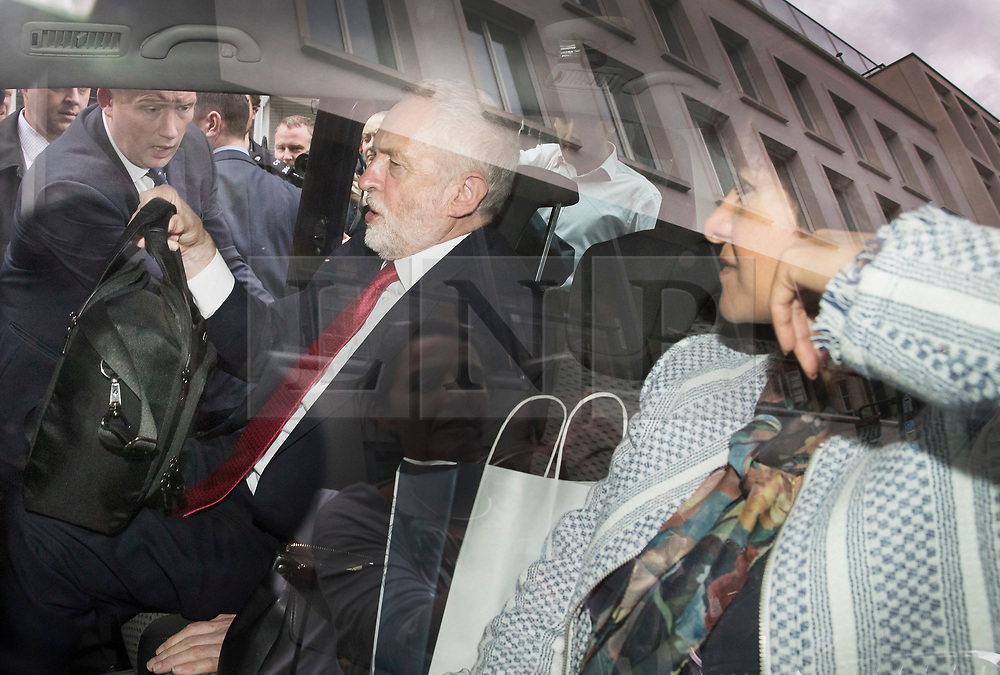 © Licensed to London News Pictures. 12/05/2017. London, UK. Labour party leader Jeremy Corbyn is watched by his wife Laura Alvarez he leaves Chatham House by car after outlining his national security and foreign policy in a speech. The general election is on June 8, 2016. Photo credit: Peter Macdiarmid/LNP