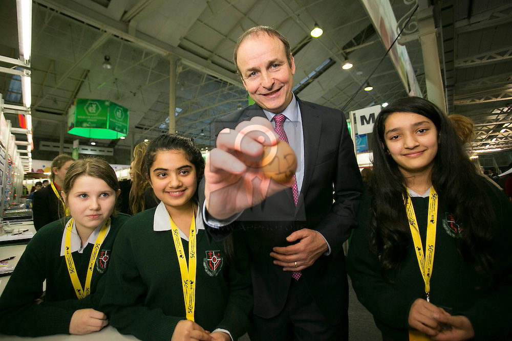 """Repro Free: 08/01/2014 <br /> Fianna Fail leader Micheál Martin TD is pictured with Amy Fitzgerald, Benushila Tripathi and Samiksha Paudel from St Aloysius School, Cork and their project """"How fresh are your egs"""" at the BT Young Scientist & Technology Exhibition 2014 in the RDS Dublin. Picture Andres Poveda"""
