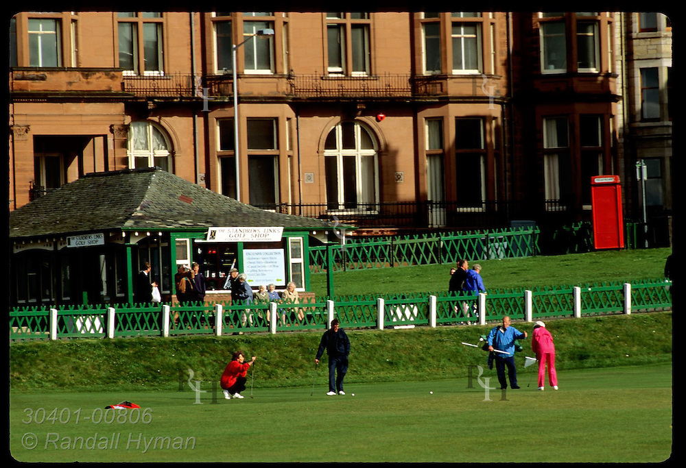 Woman in fuchsia sweatsuit putts on eighteenth hole of the famous Old Course at St. Andrews Links. Scotland