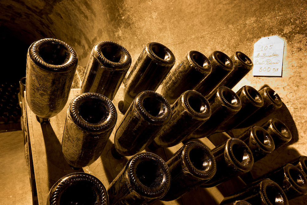 Methusalem bottles of champagne brut reserve in frames for remuage turning in caves of Champagne Taittinger in Reims, France