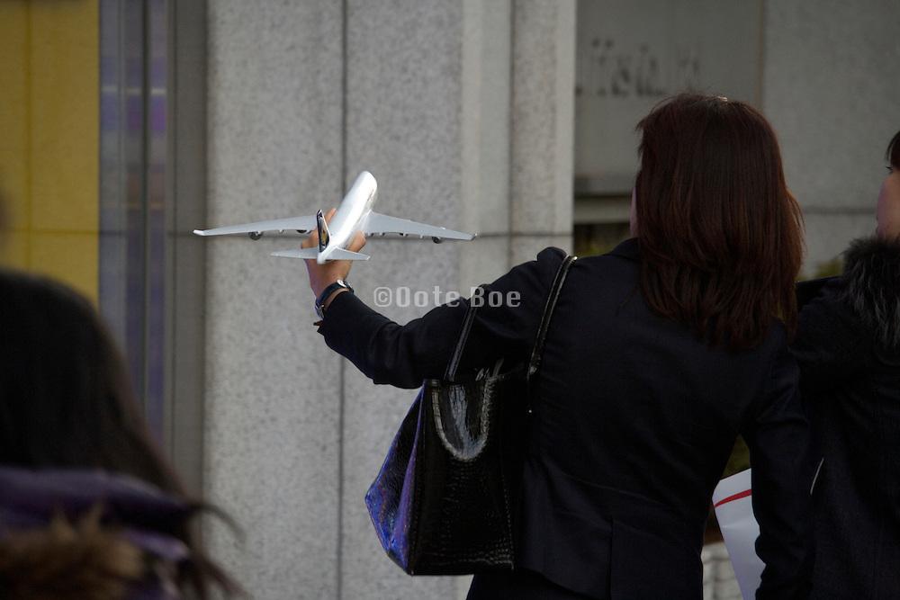 woman holding up small model passenger jumbo jet airplane