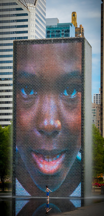 Crown Fountain is an interactive work of public art and video sculpture featured in Chicago's Millennium Park, which is located in the Loop community area. Designed by Catalan artist Jaume Plensa and executed by Krueck and Sexton Architects, it opened in July 2004. The fountain is composed of a black granite reflecting pool placed between a pair of glass brick towers. The towers are 50 feet tall, and they use light-emitting diodes (LEDs) to display digital videos on their inward faces. Construction and design of the Crown Fountain cost $17 million. The water operates from May to October, intermittently cascading down the two towers and spouting through a nozzle on each tower's front face.