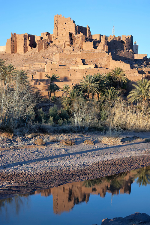 Kasbah Tiffoultoute with river and water reflection against clear blue sky.