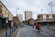 Young family walking past a small shopping area, most of which is closed down and near tower blocks of social housing in Highgate, the inner city area of Birmingham which is virtually deserted under Coronavirus lockdown on 29th April 2020 in Birmingham, England, United Kingdom. Coronavirus or Covid-19 is a new respiratory illness that has not previously been seen in humans. While much or Europe has been placed into lockdown, the UK government has put in place more stringent rules as part of their long term strategy, and in particular social distancing.