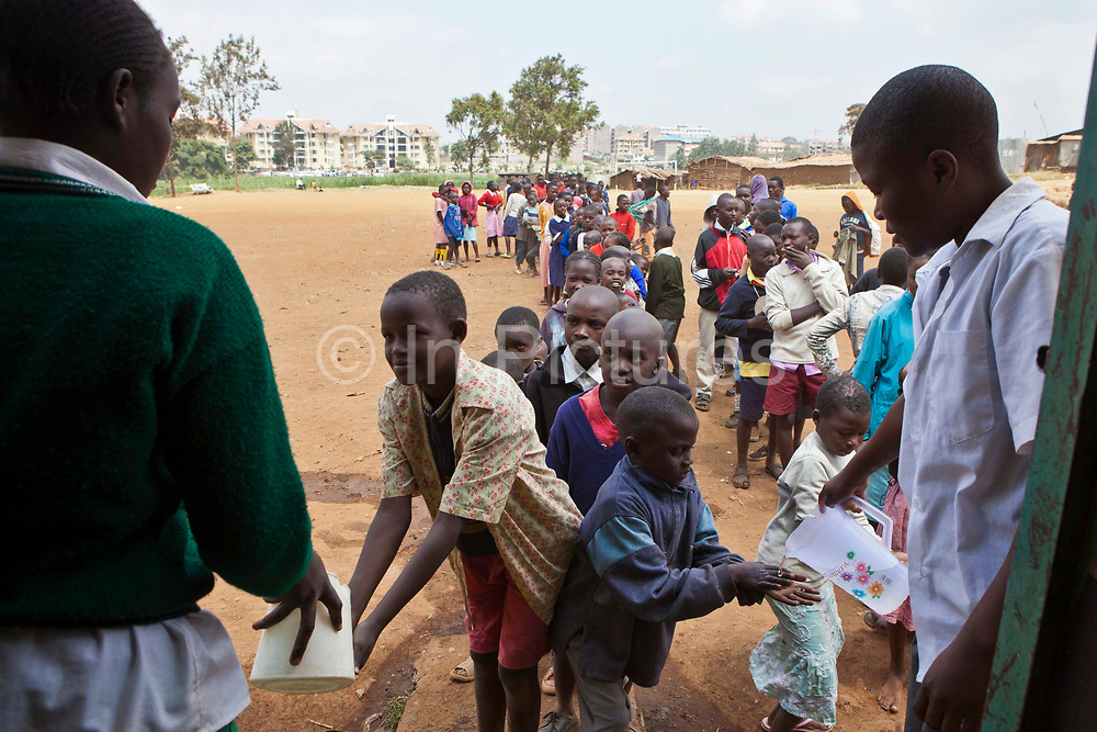 The children queuing for food and getting their hands washed at lunchtime at Kibera School, Nairobi. The school consists of 6 teachers with approximately 60 children in each class.  Undugu Society of Kenya (USK), an NGO  run various programmes to help the school and pupils including a lunchtime feeding program.