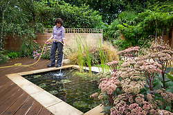 Topping up water in a pond using a hosepipe