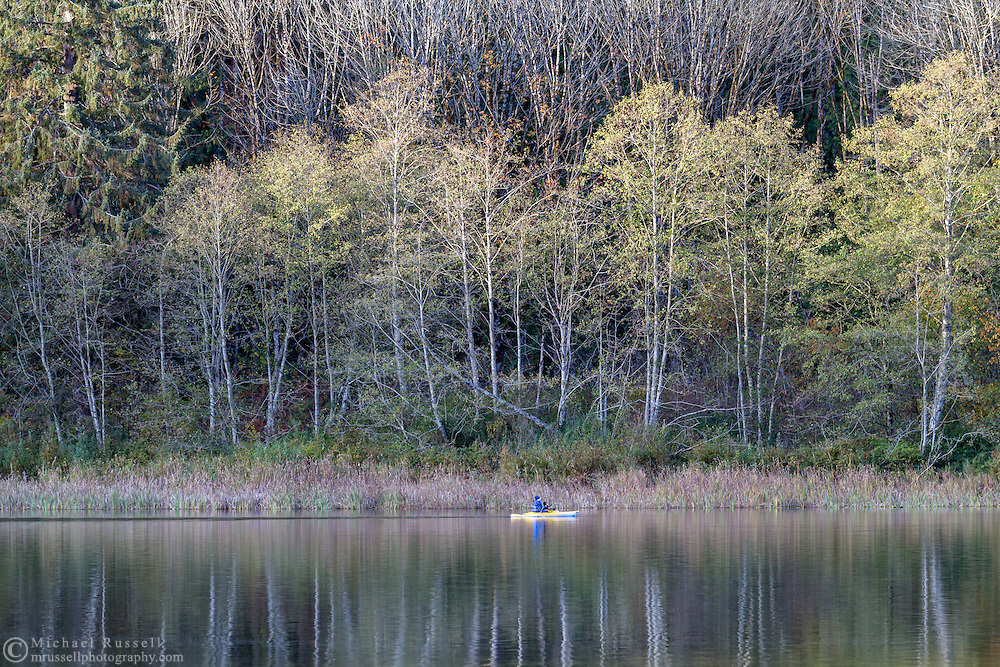 A man in a kayak explores the shore of Deer Lake in Sasquatch Provincial Park, British Columbia, Canada.