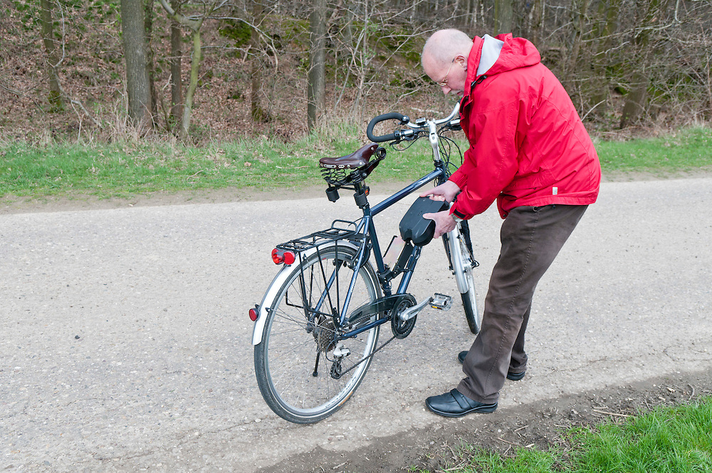 Ein Mann im Rentenalter setzt den Akku seines Elekrofahrrads ebike  ein|a man puts the batterie of an e-bike in place    |