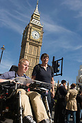 Londoners and visitors pass beneath Big Ben (now called Elizabeth Tower after the Queen's Golden Jubilee) at the Palace of Westminster, the location of Britain's parliament and government. Seen from a low angle at almost pavement level, we see a lady accompanying a teenage disabled boy in an electric wheelchair - both making their way into Parliament Square and underneath London's most well-known landmark in the heart of the UK governmental district of Westminster.