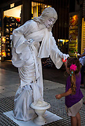 Mime artist - woman dressed as a stone statue gives illuminated heart to girl, Buenos Aires, Argentina.