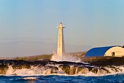 big ocean waves, pounding on lava rocks and lighthouse at Keahole Point, NELHA Facility behind and Haleakala of Maui in background, Kona Coast, Big Island, Hawaii, USA, Pacific Ocean