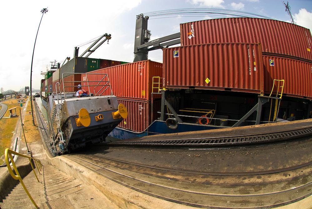 Locomotives pull a container ship through the Miraflores Locks, Panama Canal, Panama