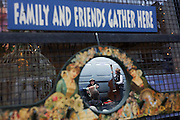 Street musicians play in Columbia Street market, seen through a shop's mirror where friends and family may gather.