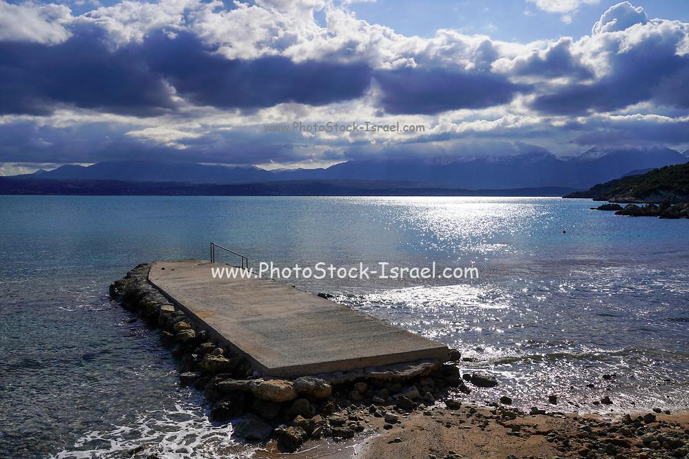 Dramatic winter mountain landscape scene on Crete, Greece. The Mediterranean Sea in the background