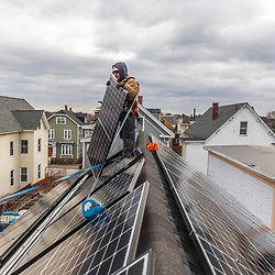 Revision Energy employee Elvis Santos installing solar panels on a multi-family home in Lowell, Massachuetts.
