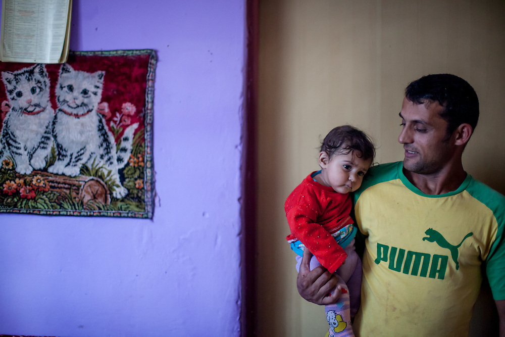 """A resident with his chlid is listening to the local Gospel band rehearsing inside a house at the Roma part at the district """"Podsadek"""". The town of Stara Lubovna has a population of 16350, of whom 2 060 (13%) are of Roma origin. The majority of Roma live in the Podsadek district, where 980 (74%) out of 1330 inhabitants are Roma."""