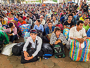 16 JUNE 2014 - ARANYAPRATHET, THAILAND: Cambodian migrant workers fleeing Thailand wait to be processed by Thai immigration police in Aranyaprathet, Thailand before being returned to Cambodia. More than 150,000 Cambodian migrant workers and their families have left Thailand since June 12. The exodus started when rumors circulated in the Cambodian migrant community that the Thai junta was going to crack down on undocumented workers. About 40,000 Cambodians were expected to return to Cambodia today. The mass exodus has stressed resources on both sides of the Thai/Cambodian border. The Cambodian town of Poipet has been over run with returning migrants. On the Thai side, in Aranyaprathet, the bus and train station has been flooded with Cambodians taking all of their possessions back to Cambodia. PHOTO BY JACK KURTZ
