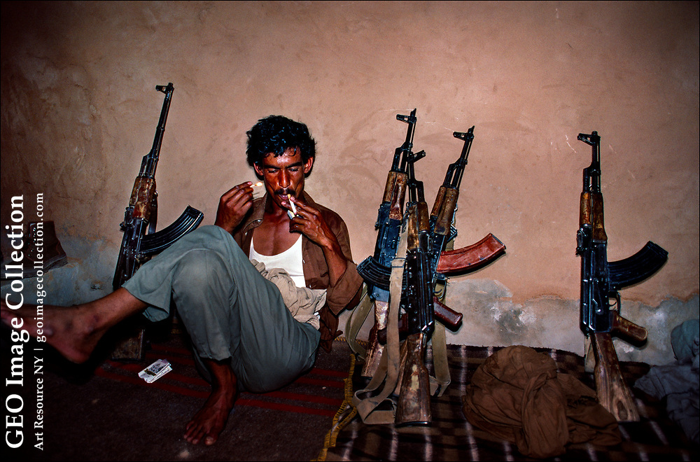 A Polisario Front guerrilla fighter, surrounded by Kalashnikov  assault rifles, steals a cigarette break in an underground bunker in the Western Sahara Desert in Morocco.