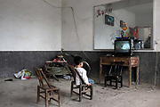 A child watches television at their home near the Changsha Xianghe Chemical Factory in Shuangqiao Village, Hunan Province, China on 13 August 2009.  The chemical plant has been shut down on suspected inadequate waste treatment that may have led to water and soil contamination that caused illness and death within the village of Shuangqiao.