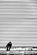 Elderly man sitting below a striped wall